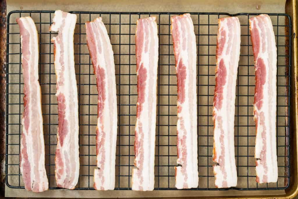 Raw bacon on a sheet pan heading into the oven.