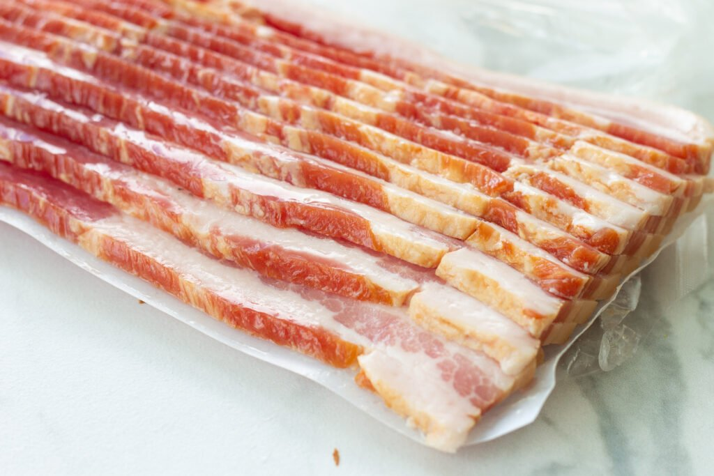 Raw bacon in package on counter.