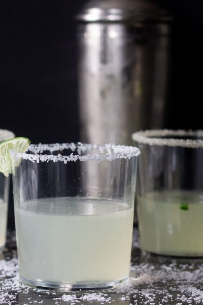 Three margarita cocktails on table with cocktail shaker, salt scattered and lime wedges.