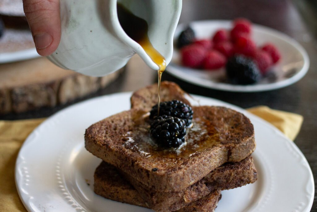 Cinnamon brioche French toast on a plate with blackberries and maple syrup drizzling onto the stack.