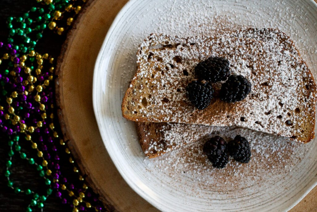 New Orlean's-style cinnamon French toast on a white plate garnished with powdered sugar.