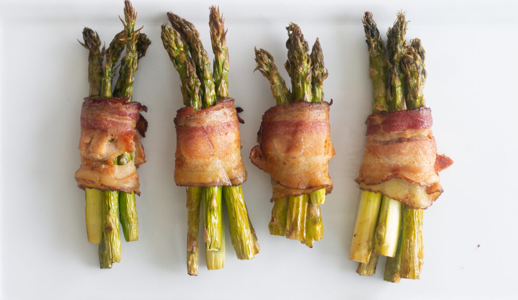 Bacon-wrapped asparagus on a white plate.