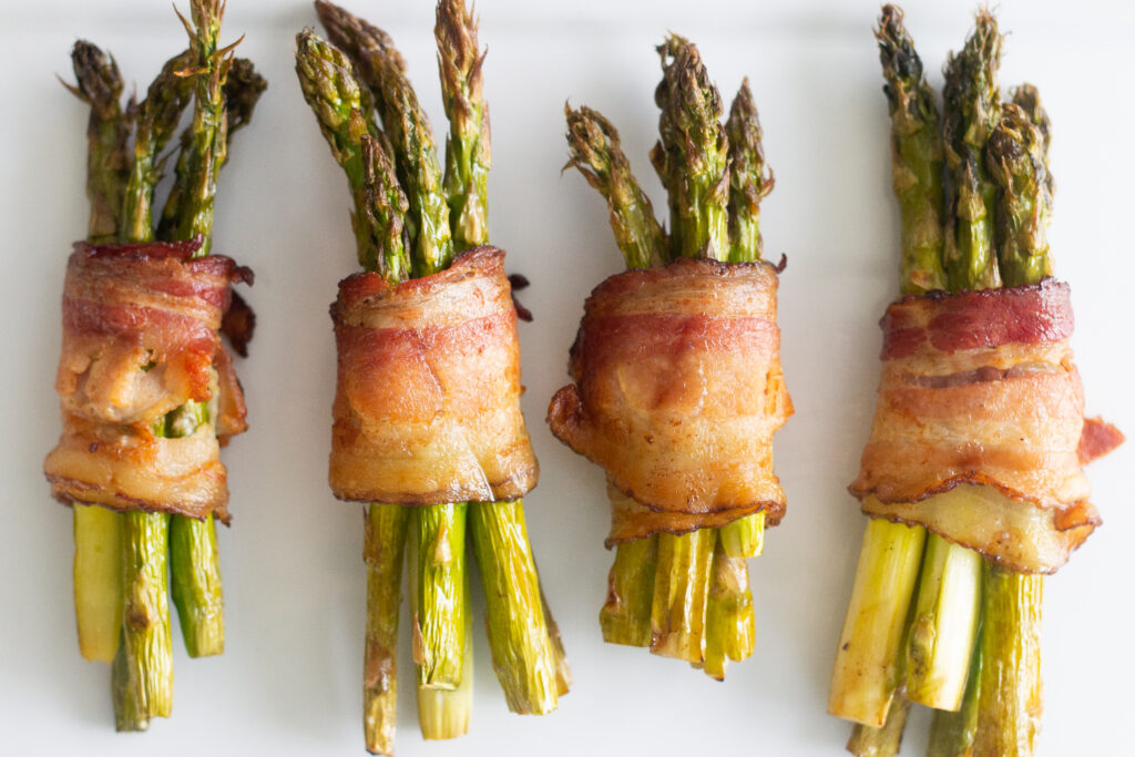 Bacon-wrapped asparagus on white plate.