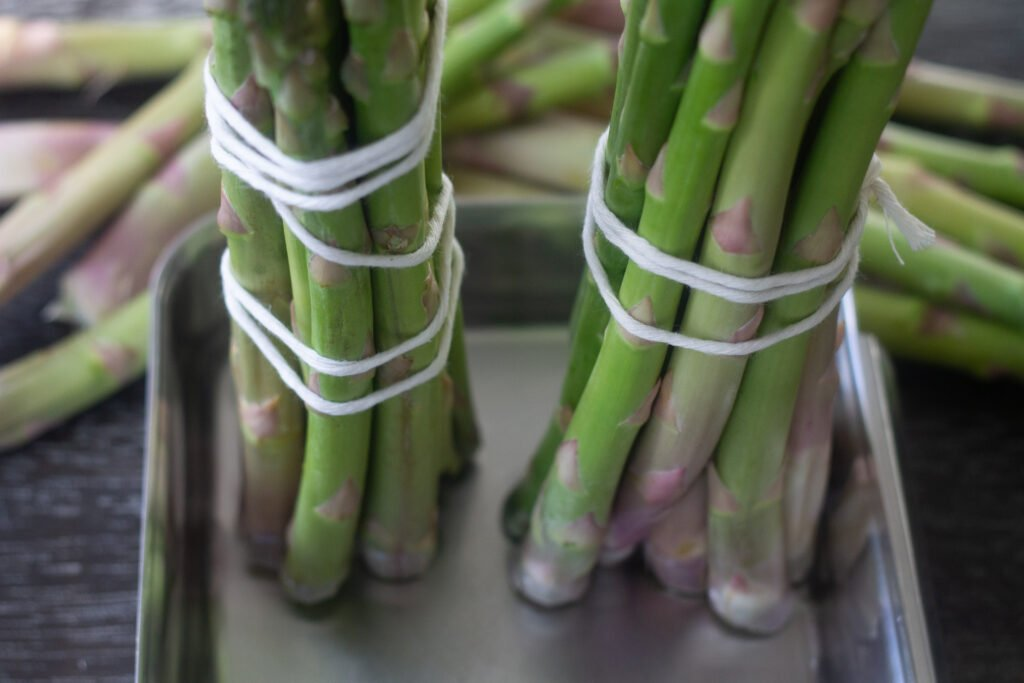 Bound bunches of asparagus sitting in a pan of shallow water.