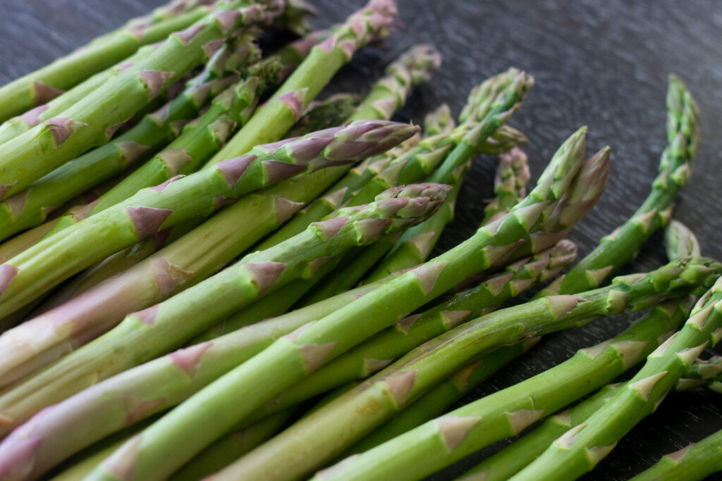 Top half of a bunch of asparagus on a table.