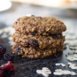 Oatmeal-raisin gluten-free lactation cookies on table next to oats and dried fruit.