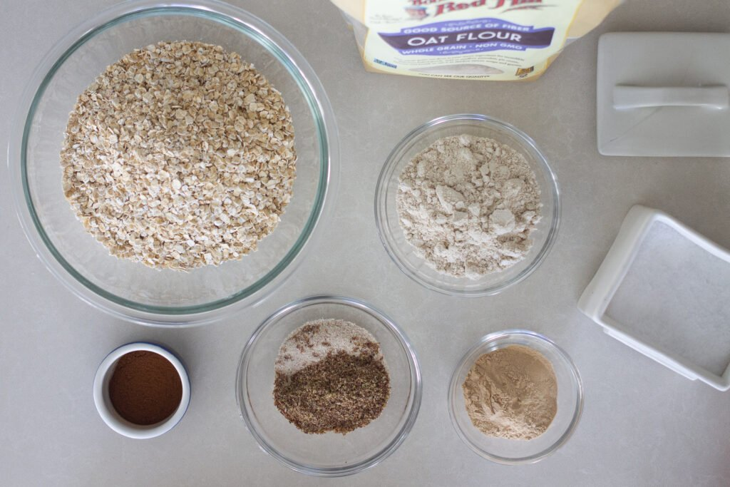 Lactation cookie ingredients on counter in glass bowls.