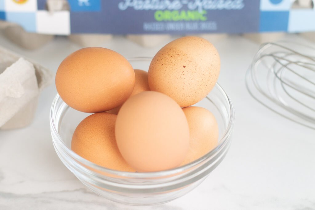 Brown eggs for how to make scrambled eggs in glass bowl on counter next to whisk and carton of