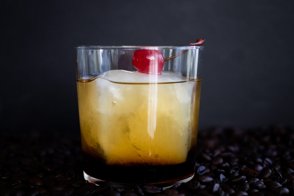 A black russian cocktail in a rocks glass with a cherry on top