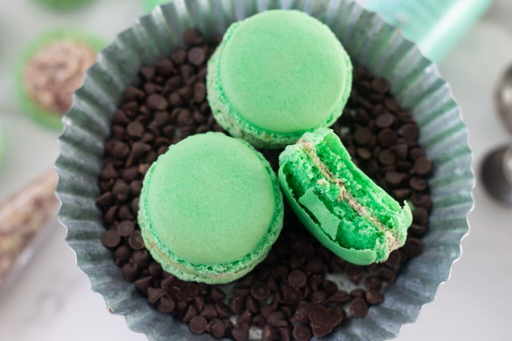 Mint chocolate chip macarons on top of mini chocolate chips.