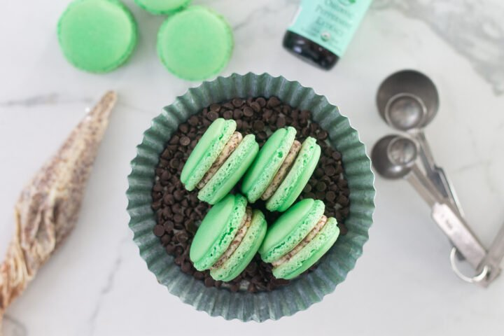 Green, mint chocolate chip macarons with a chocolate chip buttercream filling on small cake dish, on counter next to piping bag.