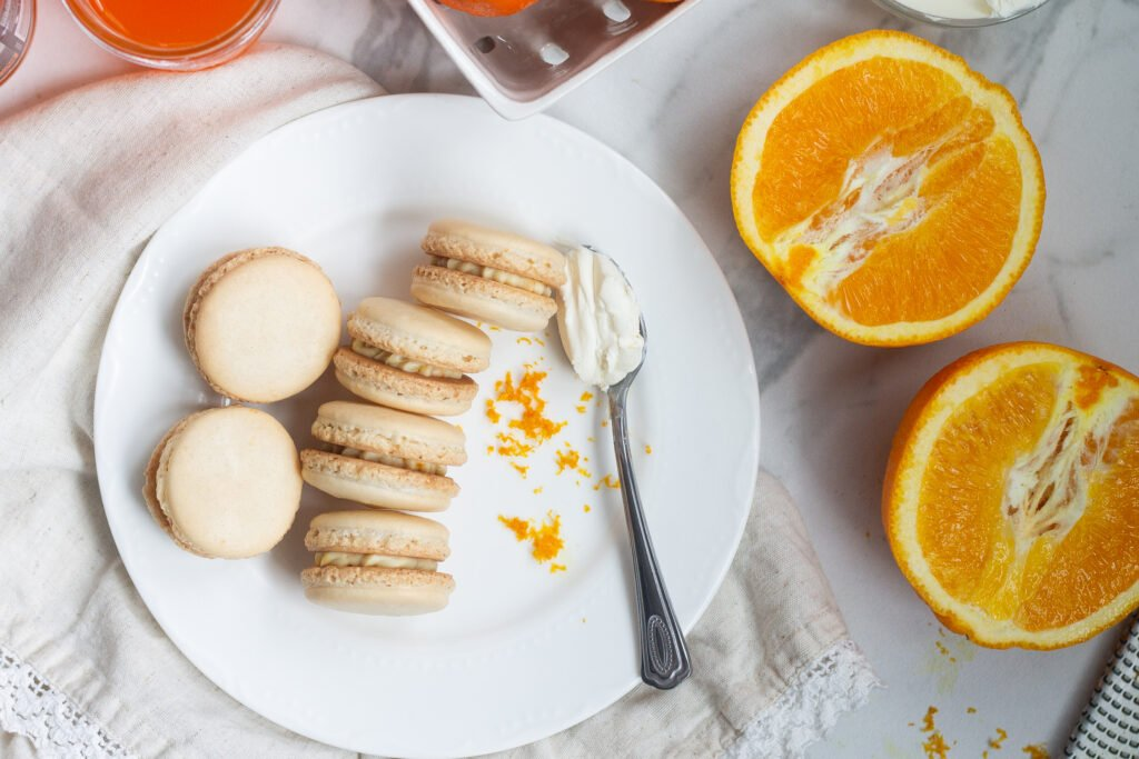 Orange creamsicle macarons on a white plate with orange zest and mascarpone cheese, next to a cut open navel orange.
