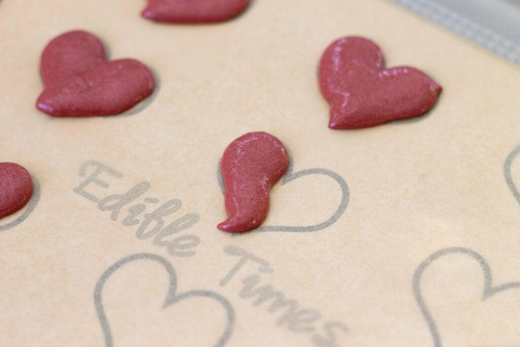 Using a macaron template to pipe heart-shaped macarons macarons