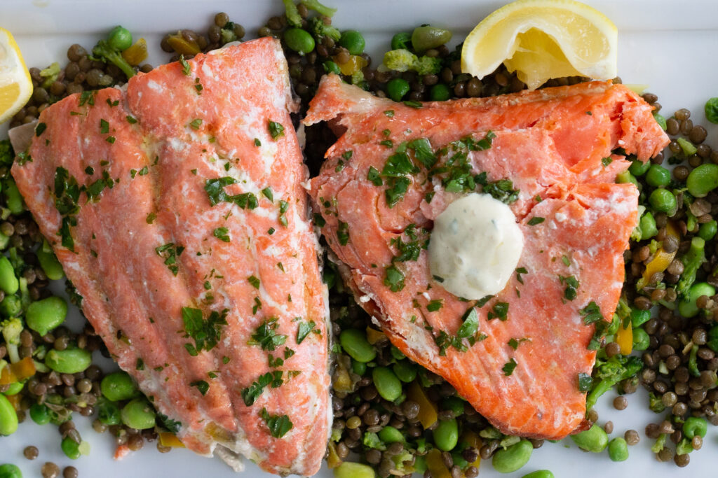 Two cooked fillets of salmon, one with dijonnaise on top.