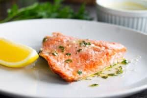 Lemon and herb roasted sockeye salmon on white plate with lemon.