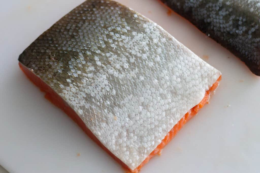 Fillet of salmon skin-side up on white cutting board.