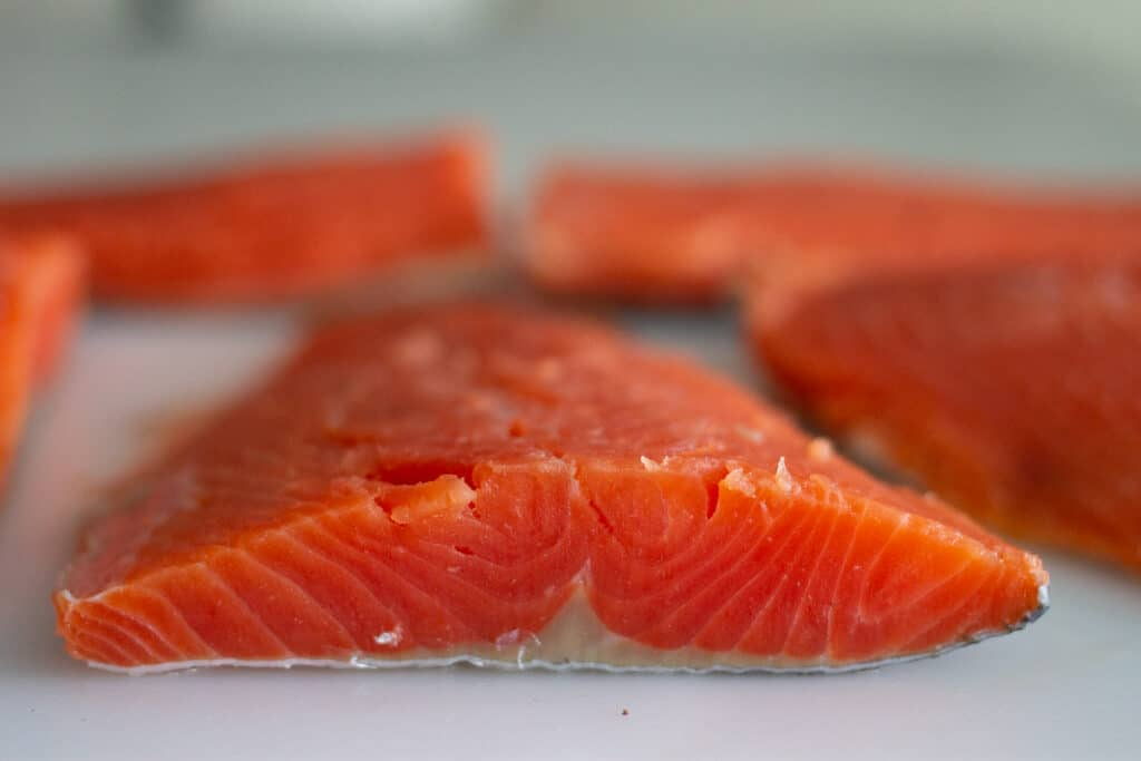 Close up of sockeye salmon fillet on cutting board.