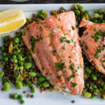 Baked sockeye salmon with herbed lemon vinaigrette on a bed of green vegetables.