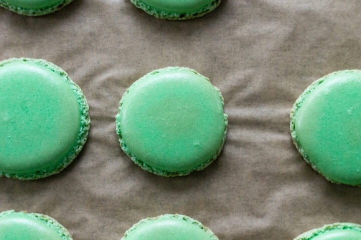 Green macaron shells on parchment paper.