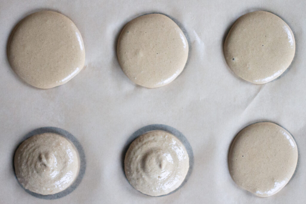 Macaron batter piped in circles on parchment paper.