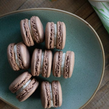 Chocolate French macarons on green plate.