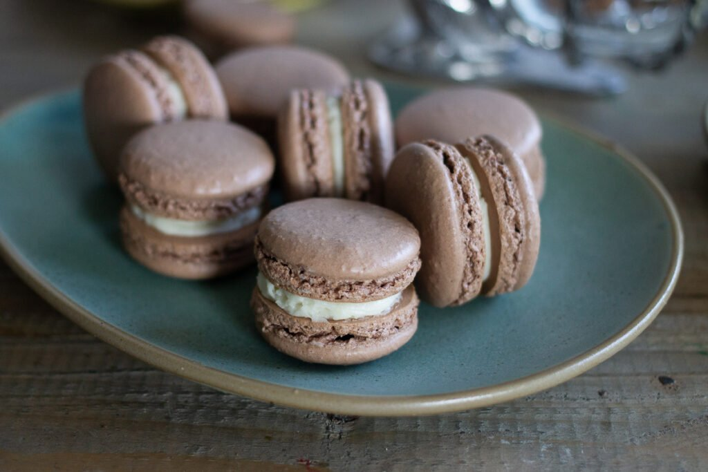 Chocolate French macarons with vanilla buttercream on green plate.
