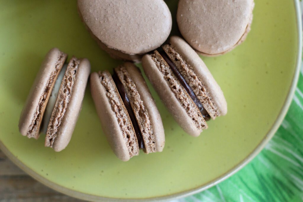Chocolate French macarons withe assorted fillings on yellow plate.