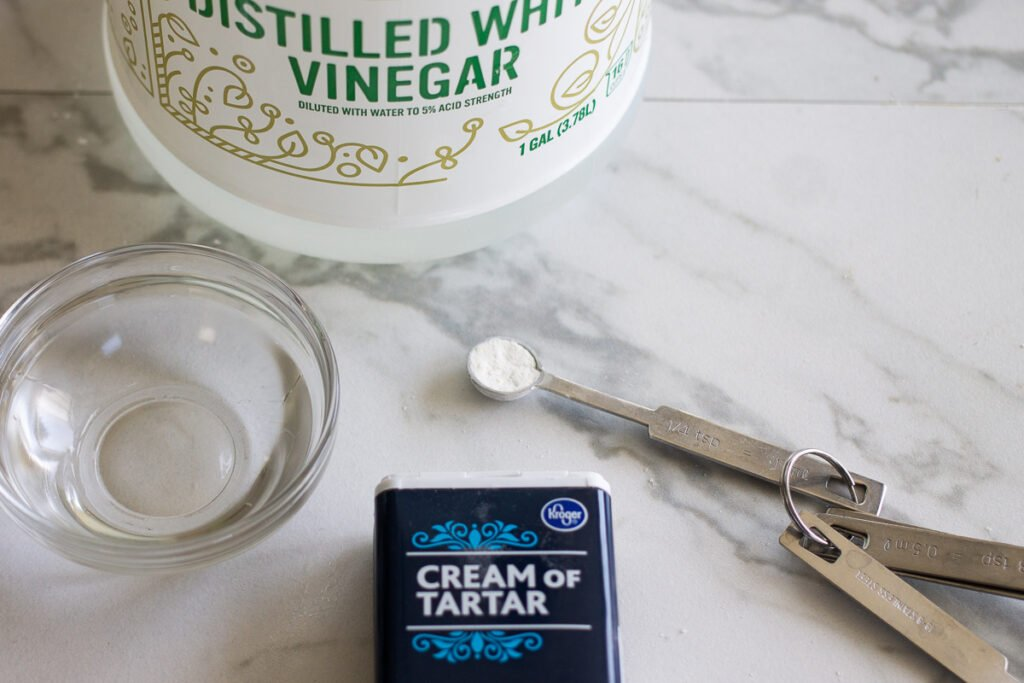 Cream of tartar container and vinegar on a counter.