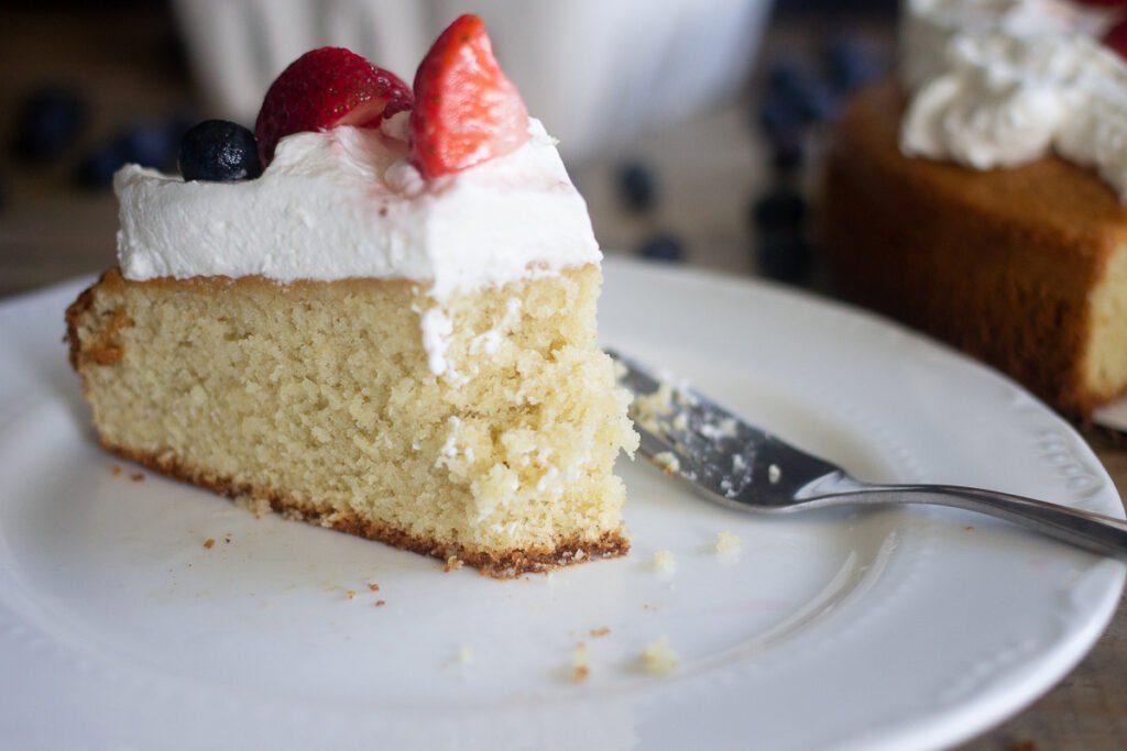 Slice of gluten-free vanilla cake with whipped cream and berries on a plate, with a bite taken out of it.