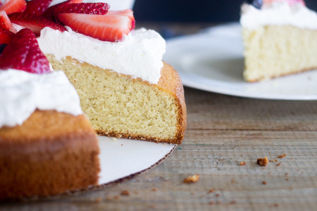 Close up of vanilla cake with whipped cream and strawberries on top, on part of cake where slice is cut out.