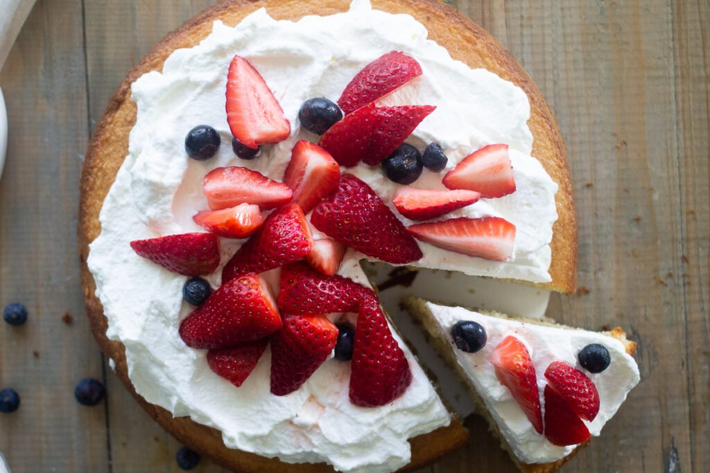 Looking down on a single layer gluten-free vanilla cake with whipped cream and berries on top.