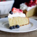 Slice of gluten-free vanilla chiffon cake on a white plate with whipped cream and berries on top.