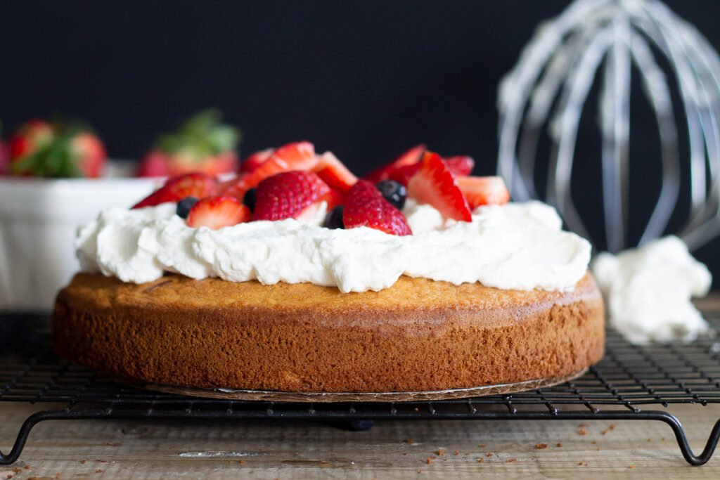 Looking at a gluten-free vanilla cake with whipped cream and berries from the side, sitting on a cooling rack.