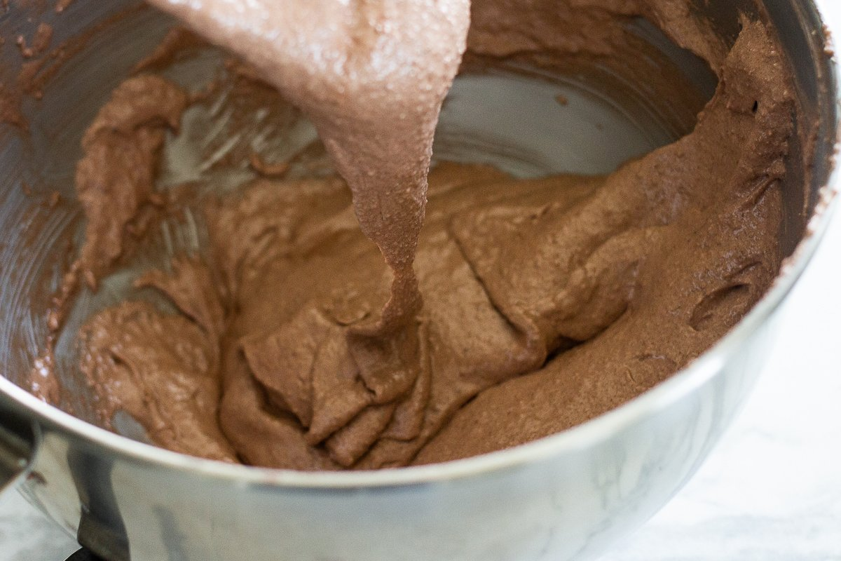Chocolate macaron batter in large mixing bowl, flowing slowly off a spatula.