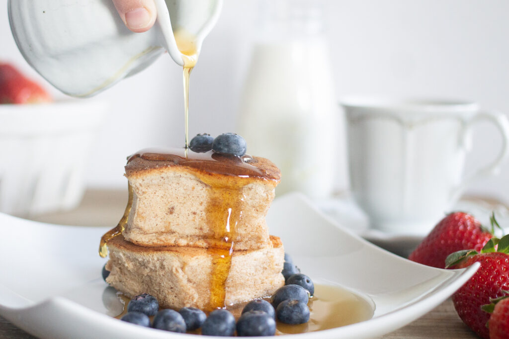 Japanese souffle pancakes on plate with syrup and blueberries