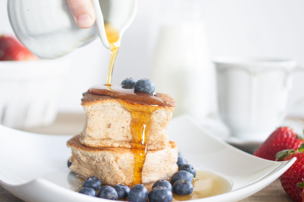gluten-free Japanese souffle pancakes on plate with maple syrup drizzling on top.