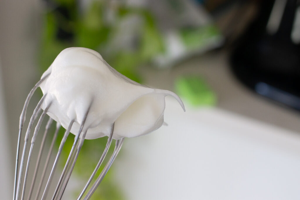 Whipped soft peak meringue on a whisk.