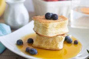 Japanese souffle pancakes on plate with blueberries and maple syrup.
