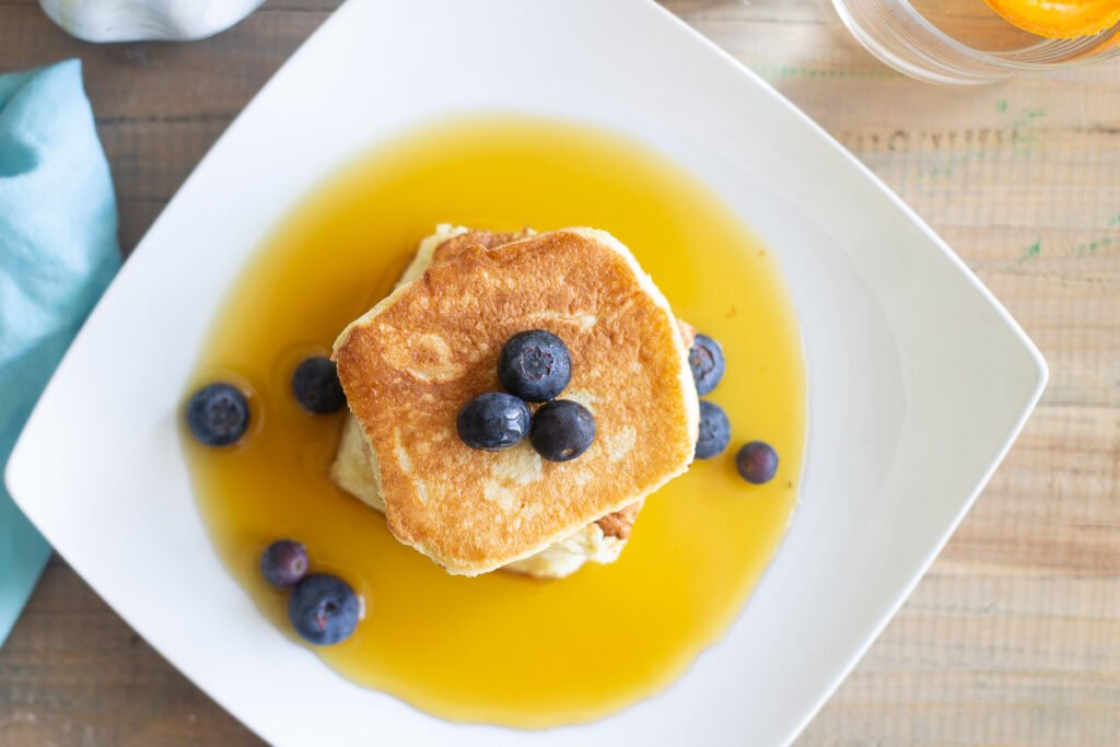 Looking down on Japanese souffle pancakes on plate with maple syrup and blueberries.