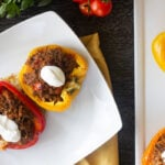 Keto stuffed peppers in a white plate, next to more on a platter.