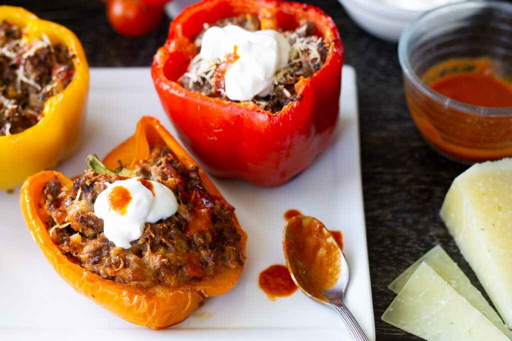 Enchilada-style low-carb stuffed peppers on white plate with enchilada sauce drizzle