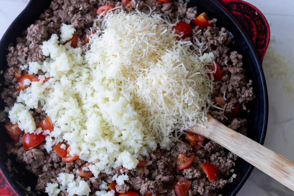 Low-carb stuffed pepper meat filling in cast iron skillet with mounds of cauliflower rice and Parmesan on top.