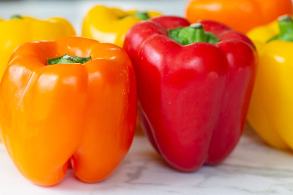 Orange, red and yellow bell peppers on counter.