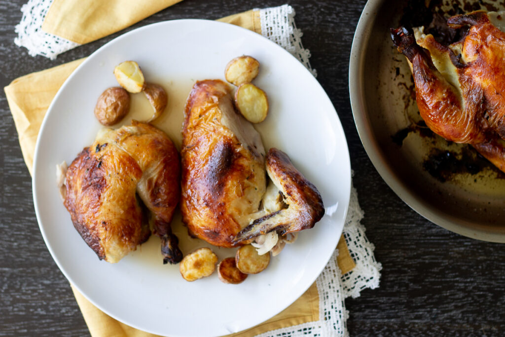 Roasted chicken carved on a plate with small roasted potatoes.