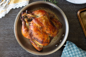 Whole roasted chicken with a deep golden color in a sauté pan on table.