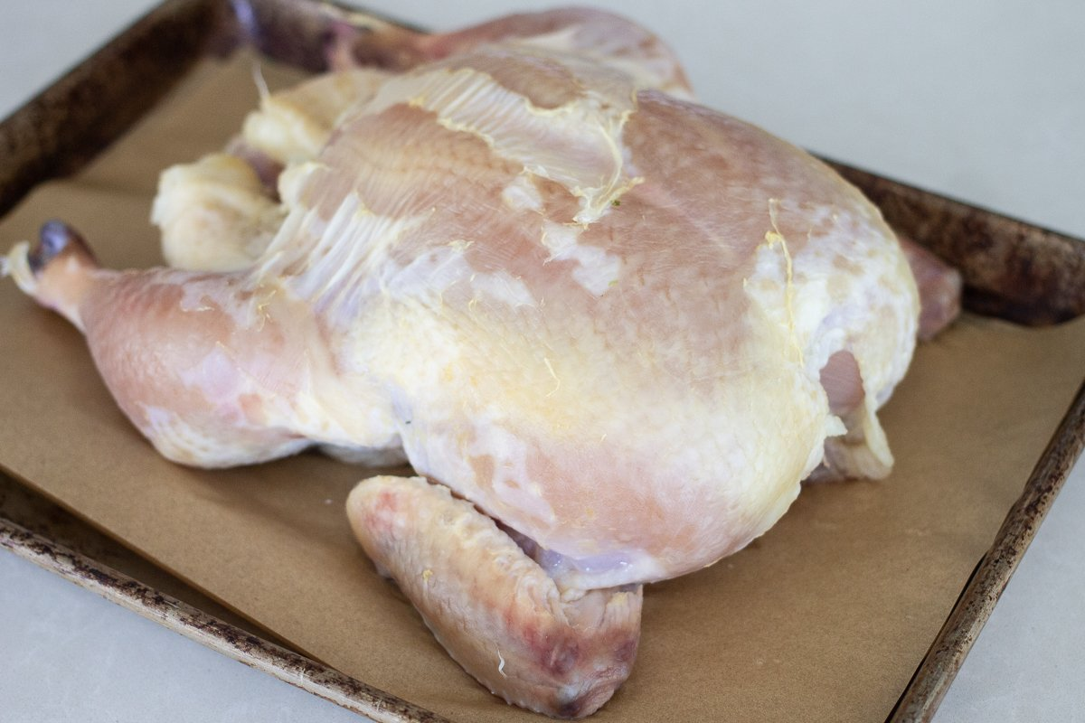 Brined and dried out whole chicken on small parchment-lined sheet pan. Skin has turned translucent.